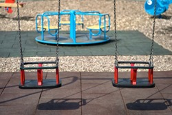 Two rubber swings weigh on a chain. Playground on a sunny day, shadow from the swing. Seats on the swing are free, there are no children on the Playground