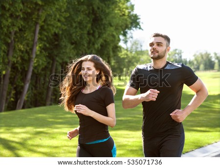 Two runners sprinting outdoors - Sportive people training in a urban area, healthy lifestyle and sport concepts