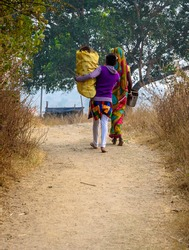 Two rural Women Carrying Cow Dung .