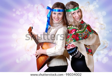 Two russian beauties with folk attributes on the shining light background