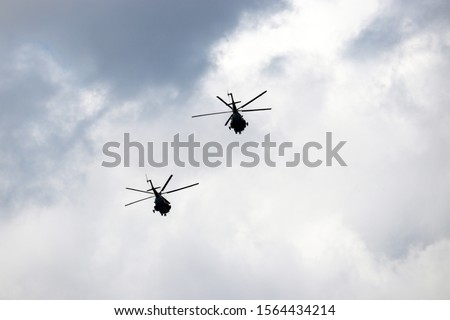 Two russian military helicopters in flight, silhouettes on background of cloudy sky. Air forces of Russia