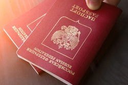 Two russian passports in hand in the sunlight. Toned.