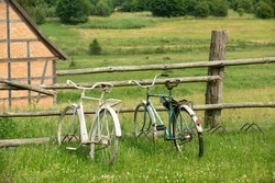 Two rusty village bikes leaning agains a wooden fence