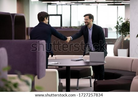 Two 35s Caucasian businessmen in formal suits at meeting shake hands express respect. Concept of parties succeed agreement, start job interview in modern office, business etiquette, greeting gesture