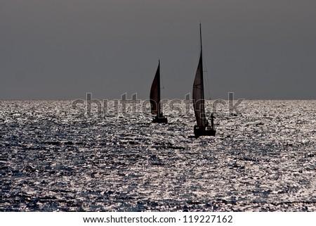 Two sailing boats sailing at sea. - stock photo