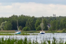 Two sailing yachts sail on a shallow river against the background of a forest. summer day, sailing in the Moscow region, outdoor activities, water sports, view from the Moscow canal.
