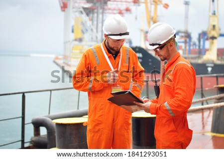 Two sailors in orange overalls work on the ship with documents.