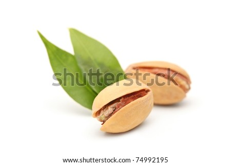 Two salted and roasted pistachio nuts with shell and green leaves isolated on white background