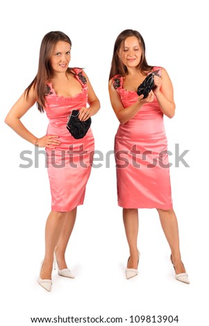 Two same women wearing pink evening dress in studio on white background. First woman looks at camera and second woman looks at handbag.