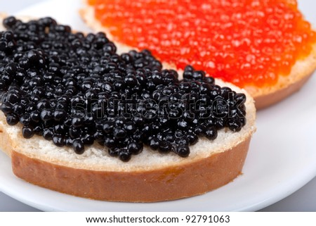 two sandwich with red and black caviar on plate