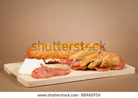 Two sandwiches wit italian sliced salami and fresh cheese over a wooden board