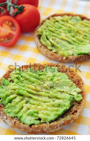 Two sandwiches with avocado on a yellow towel, tomatoes in the background