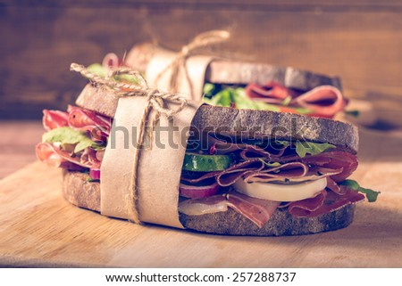 Two sandwiches with bacon and fresh vegetables on vintage wooden cutting board.  In the style of instagram filter. Close-up.