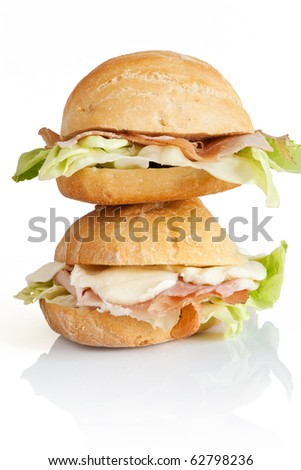 two sandwiches with ham, lettuce and mozzarella isolated on white background with clipping path - stock photo