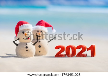 Two Sandy Christmas Snowmen are celebrating a Happy New Year on a beautiful beach with 2021 3d text, concept for new year 2021