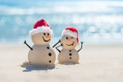 Two Sandy Christmas Snowmen are celebrating Christmas on a beautiful beach, one of them is only in focus