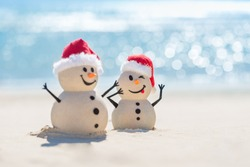 Two Sandy Christmas Snowmen are celebrating Christmas on a beautiful beach with beautiful bokeh in the background, one of them is only in focus
