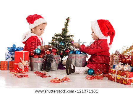two  santa helpers decorating a tree