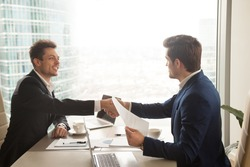 Two satisfied businessmen shaking hands at office desk after successful negotiations, business partners in formal wear handshaking, making deal, accepting offer, help, binding bargain signing contract