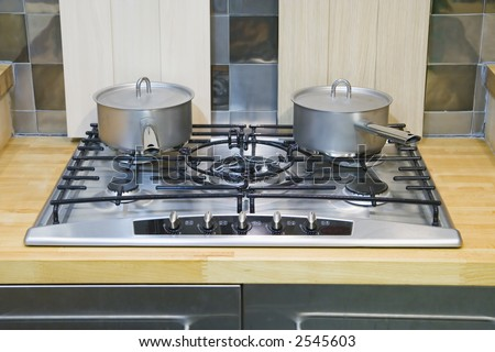 Two saucepans with lids on a gas hob