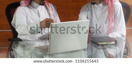 Two Saudi Businessmen Meeting, Working on a Laptop