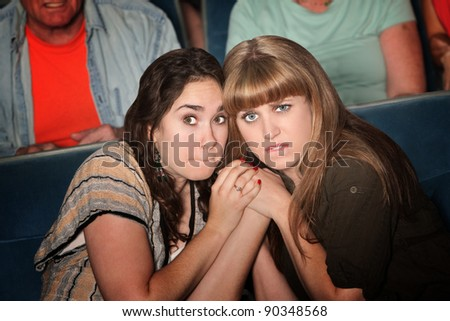 Two scared Caucasian women hold hands in theater