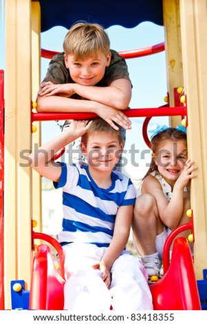 Two school aged boys and girl on the playground