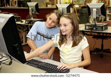 Two school children doing research together on the library computers.