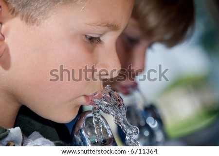 Two school children drinking from a water fountain quench their thirst during recess