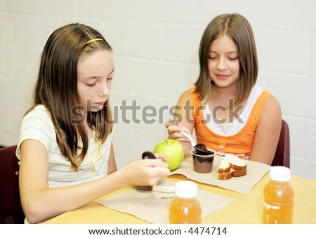 Two school girls eating lunch together in the cafeteria.