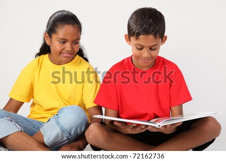 Two school kids happily reading a book