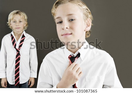 Two school kids wearing uniform with one of them tightening his tie.