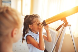 Two schoolgirls are looking through a telescope in an astronomy lesson, back to school, children's education.