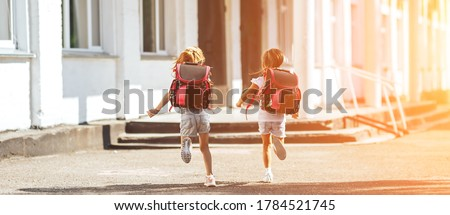 Two schoolgirls holding each other's hands run to school, back to school, primary education of children. Photo stock ©