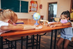 Two schoolgirls in medical masks are sitting at a school desk, opposite each other, group session, back to school, teaching children, social distance during epidemic.