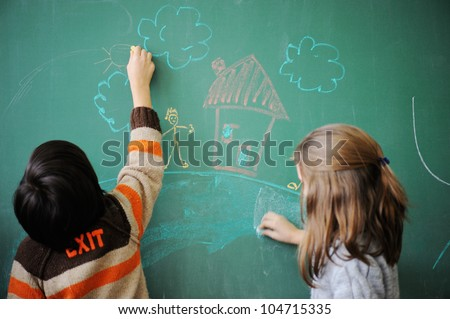 Two schoolkids wriing on blackboard