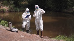 Two scientists in full biohazard suits and masks taking water samples from a river to check for hazardous pollutants or contaminants