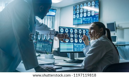 Two Scientists in the Brain Research Laboratory work on a Project, Using Personal Computer with MRI Scans Show Brain Anomalies. Neuroscientists at Work.