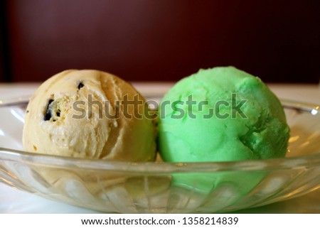 Two Scoops of Chocolate Chip and Lime Sherbet Ice Cream in a Glass Bowl