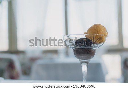 Two scoops of ice cream, mango and chocolate, in a clear glass against the background of a cozy restaurant.