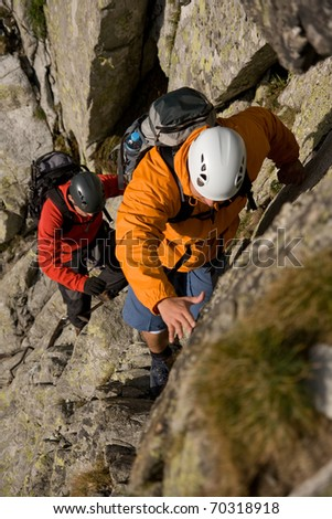 Two scramblers in helmets with backpacks climbing in mountains. Route on the Gerlach in Slovakian High Tatra Mountains.