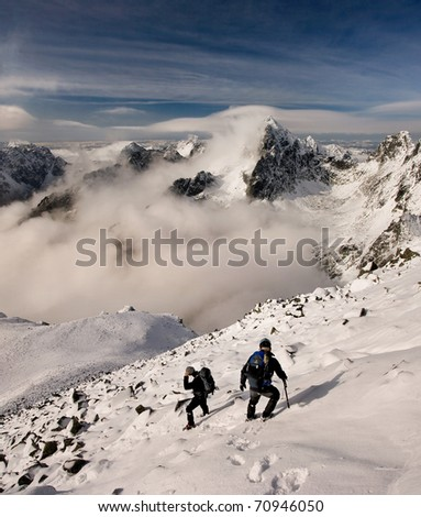 Two scramblers with backpacks going down in mountains. Winter Slovakian High Tatra Mountains.