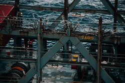 Two seafarers are standing on aft mooring station watching the ocean and fishing at dusk. Brown container, mooring winch, bollards and lashing bridge are visible. Vessel, ship, seafaring.