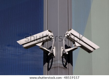 Two security cameras hanging on the building wall