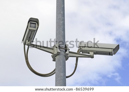 two security cameras on a street pole