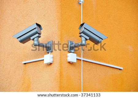 Two security cameras on two sides of building