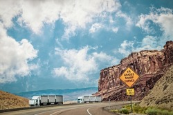 Two semi trailer trucks withthree trailers each - one broken down in canyonlands of Utah USA with sign 6% grades and sharp curves