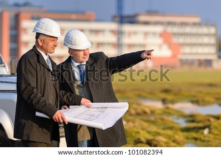 Two senior architect developers review plans at a construction site