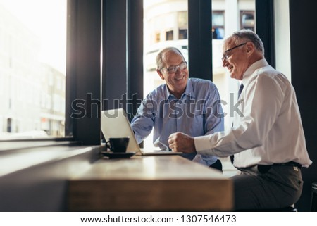 Two senior business men working together in modern cafe. Business partners sitting near window with laptop on table at restaurant.