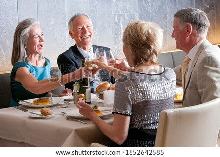 Fototapete Two senior couples on a double date enjoying together while toasting the wine glasses at a restaurant table